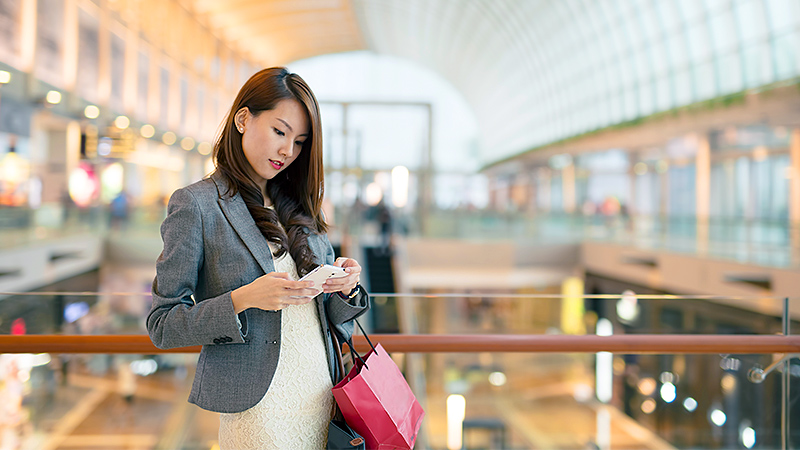 Woman standing inside a mall holding a shopping bag and looking at her mobile phone.