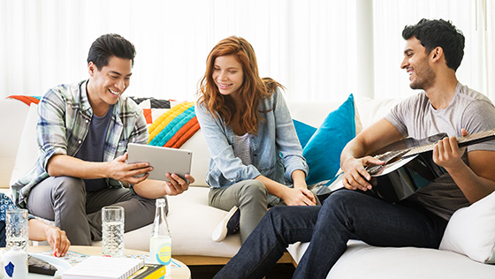 Three people sitting on a couch and looking at one person's tablet while chatting.